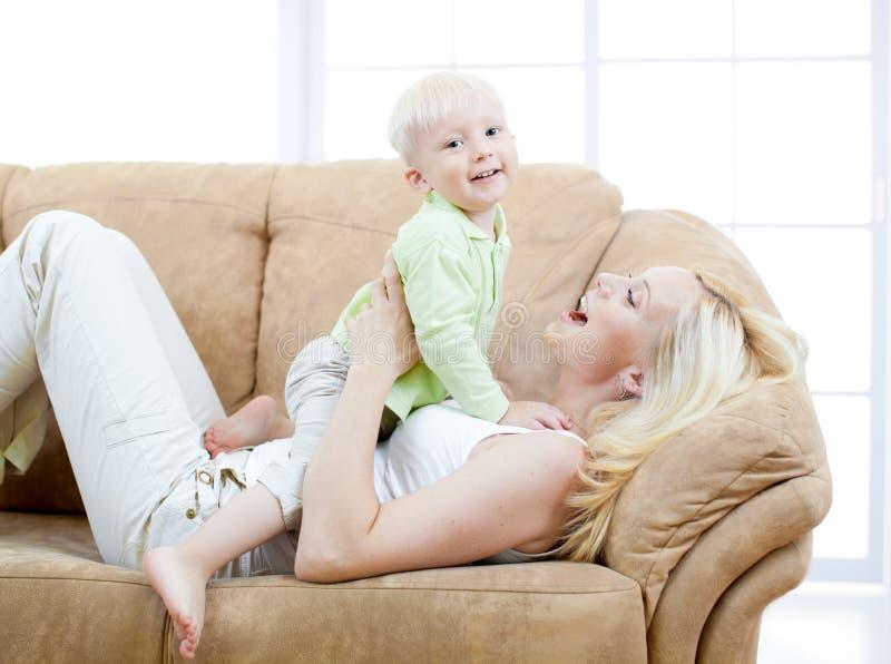 Glücklicher Sohn und Mutter, die auf Sofa spielt lizenzfreie stockbilder