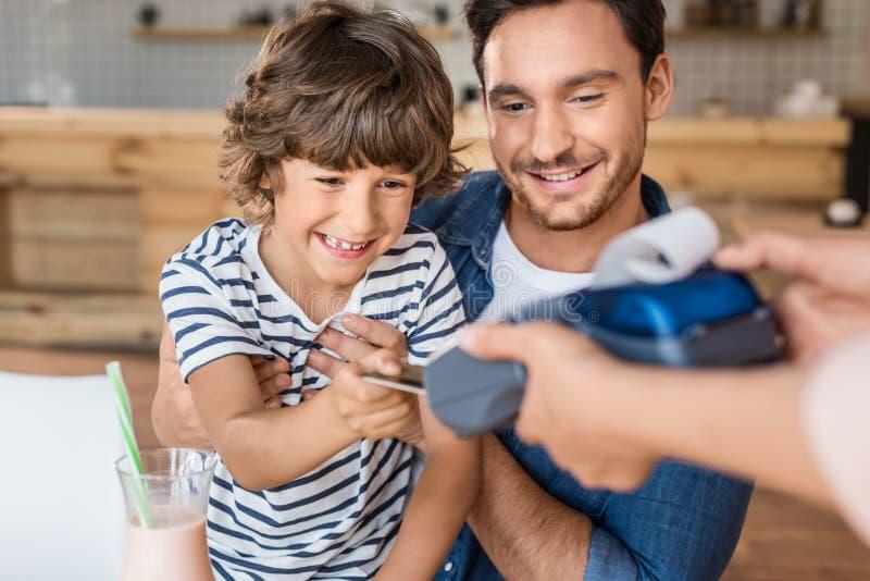 glücklicher Sohn und Vater, die mit Kreditkarte zahlt lizenzfreie stockbilder