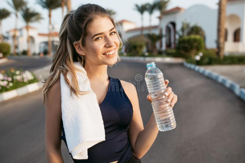 Glücklicher sonniger Morgen des Porträts der sportiven aktiven jungen Frau, die zur Kamera mit Flasche Wasser auf Straße von trop lizenzfreies stockbild