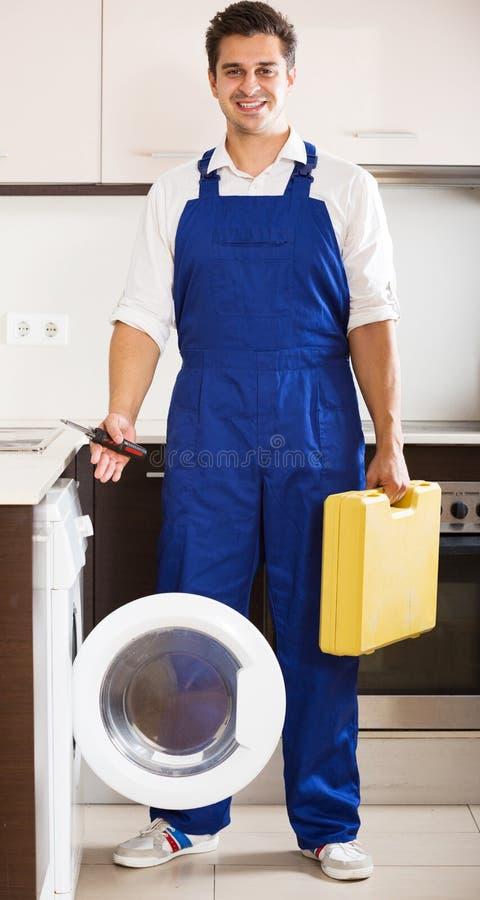 Glücklicher Spezialist mit der Bearbeitung nahe Waschmaschine stockfotografie
