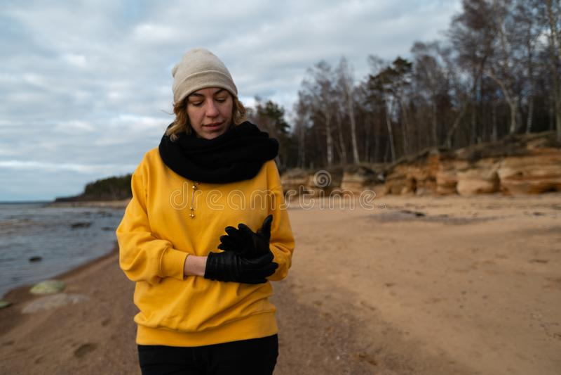 Glücklicher Sport- und Modeliebhaberenthusiast, der auf einem Strand trägt helle gelbe Strickjacke und schwarze Handschuhe und  stockfotografie