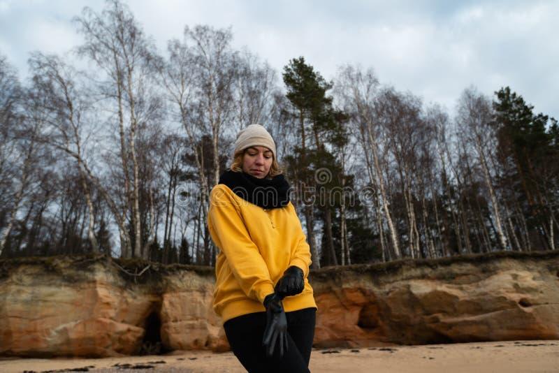 Glücklicher Sport- und Modeliebhaberenthusiast, der auf einem Strand trägt helle gelbe Strickjacke und schwarze Handschuhe und  lizenzfreie stockfotos