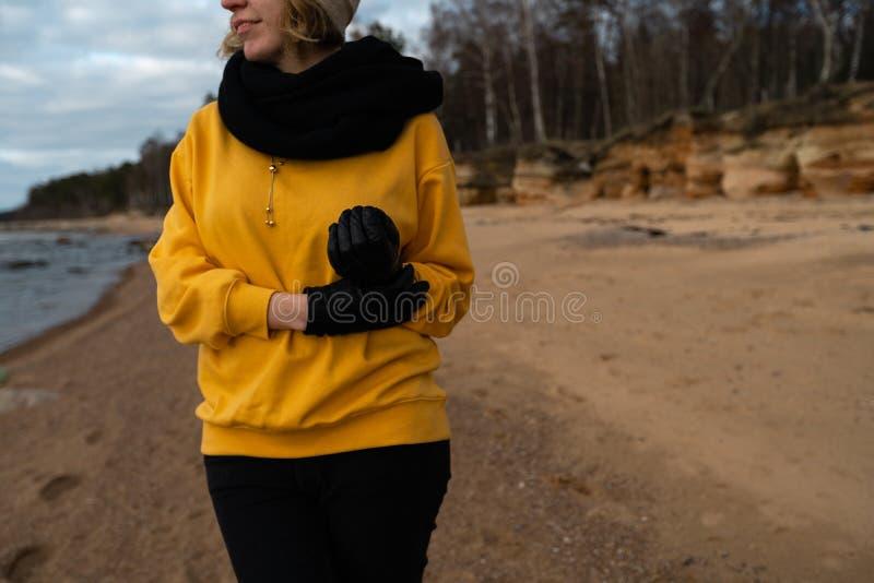 Glücklicher Sport- und Modeliebhaberenthusiast, der auf einem Strand trägt helle gelbe Strickjacke und schwarze Handschuhe und  stockfoto