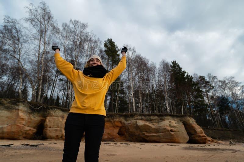 Glücklicher Sport- und Modeliebhaberenthusiast, der auf einem Strand trägt helle gelbe Strickjacke und schwarze Handschuhe und  stockbilder