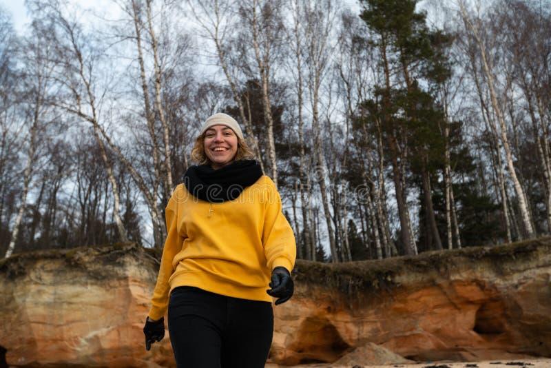 Glücklicher Sport- und Modeliebhaberenthusiast, der auf einem Strand trägt helle gelbe Strickjacke und schwarze Handschuhe und  stockfotos