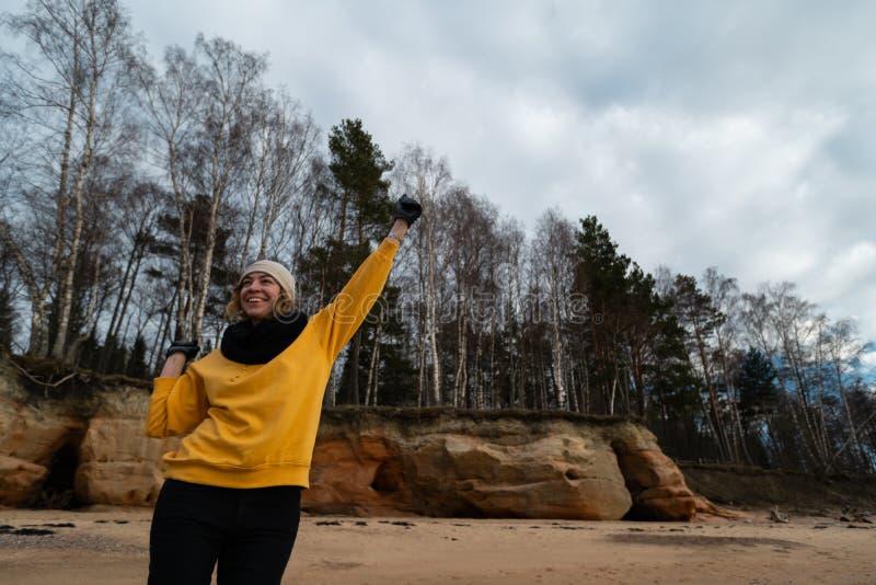 Glücklicher Sport- und Modeliebhaberenthusiast, der auf einem Strand trägt helle gelbe Strickjacke und schwarze Handschuhe und  lizenzfreie stockfotografie