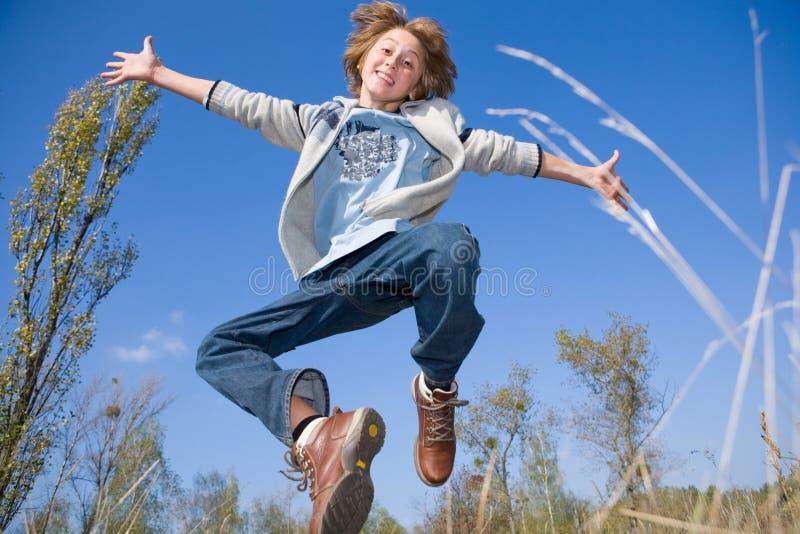 Glücklicher springender Junge stockfotografie