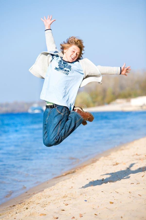 Glücklicher springender Junge auf Strand lizenzfreie stockbilder
