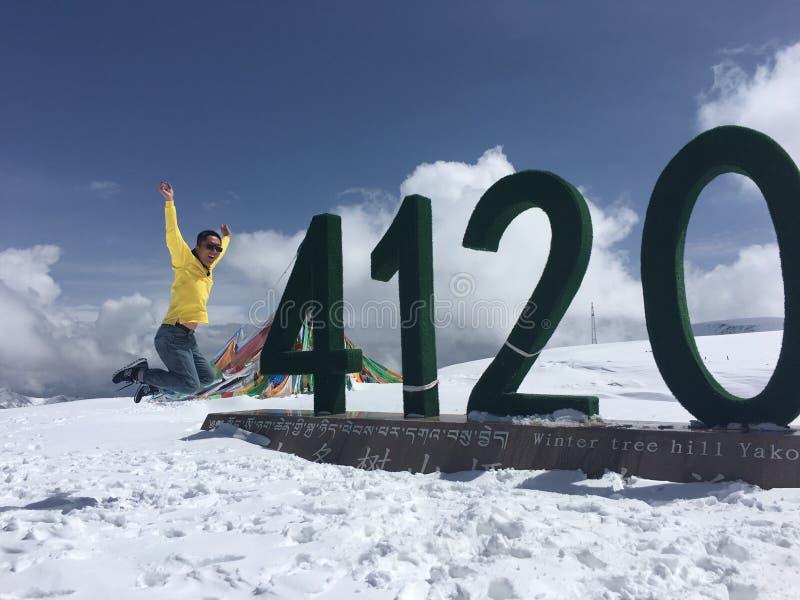 Glücklicher Sprung im Hochpass von Qinghai-See von China mit Höhe 4120 Meter im verschneiten Winter stockbilder