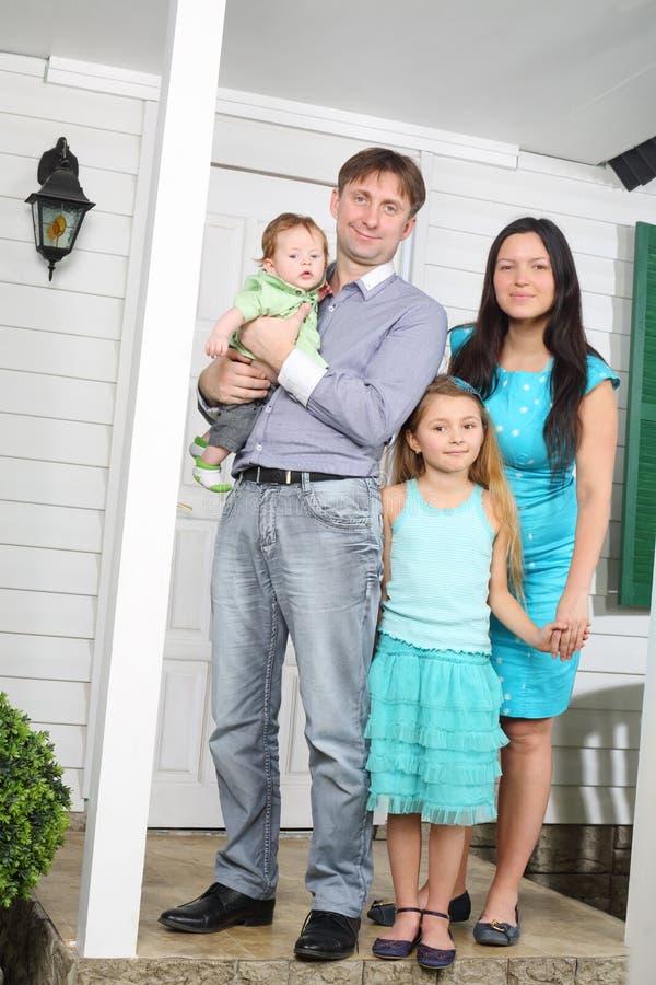 Glücklicher Stand der vierköpfigen Familie auf Portal des neuen Häuschens. lizenzfreie stockfotos