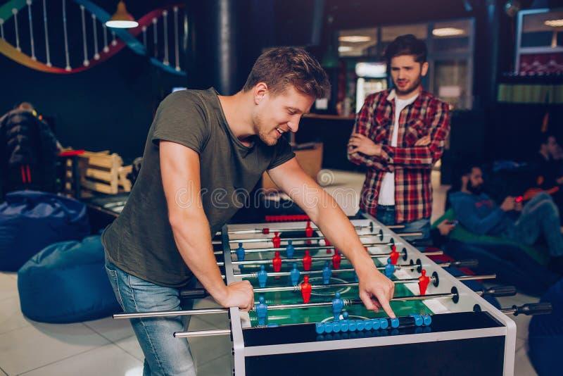 Glücklicher Stand des jungen Mannes und Fußball bei Tisch lehnen, wenn Raum gespielt wird Sein unglücklicher Freundstand hinten E stockfoto