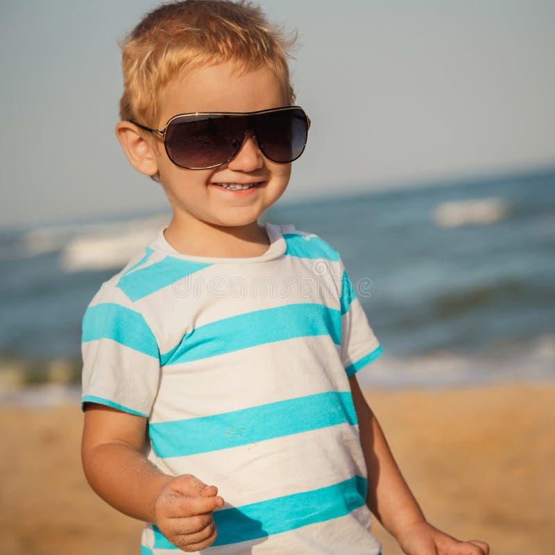 Glücklicher stilvoller Junge in der Sonnenbrille und in gestreiftem T-Shirt das Leben auf Sommerstrand genießend lizenzfreies stockfoto