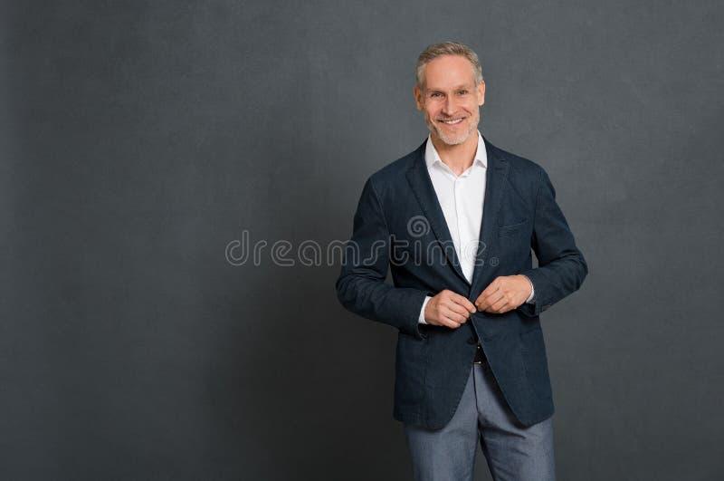 Glücklicher stilvoller Mann, der Knopf justiert stockfotos