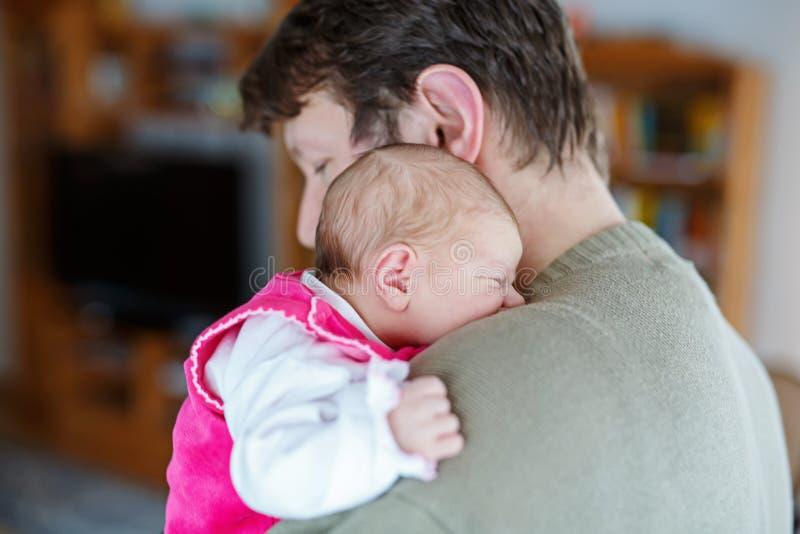 Glücklicher stolzer junger Vater, der seine schlafende neugeborene Babytochter hält lizenzfreie stockfotos