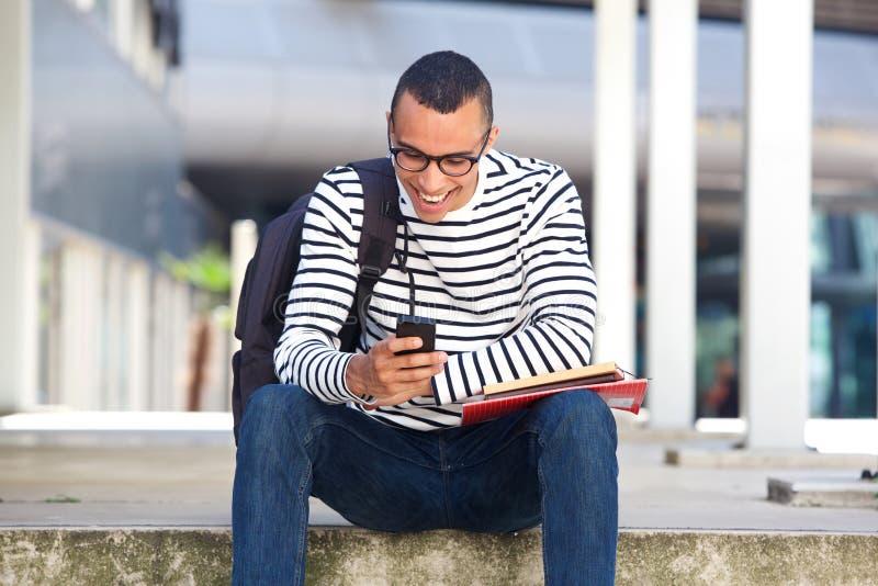 Glücklicher Student, der auf dem Campus außerhalb des Betrachtens des Handys sitzt stockbild