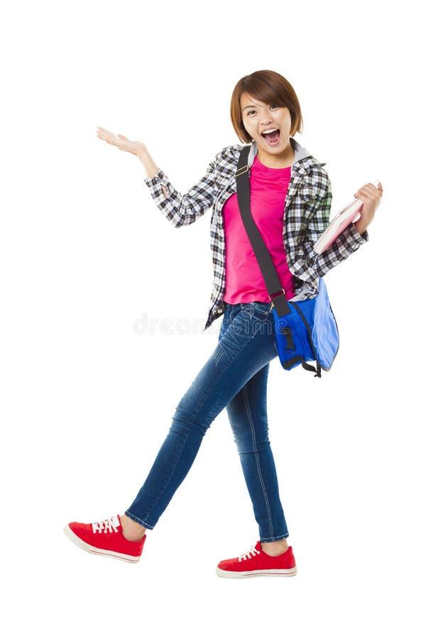 Glücklicher Student, der Bücher hält und etwas zeigt stockfotos
