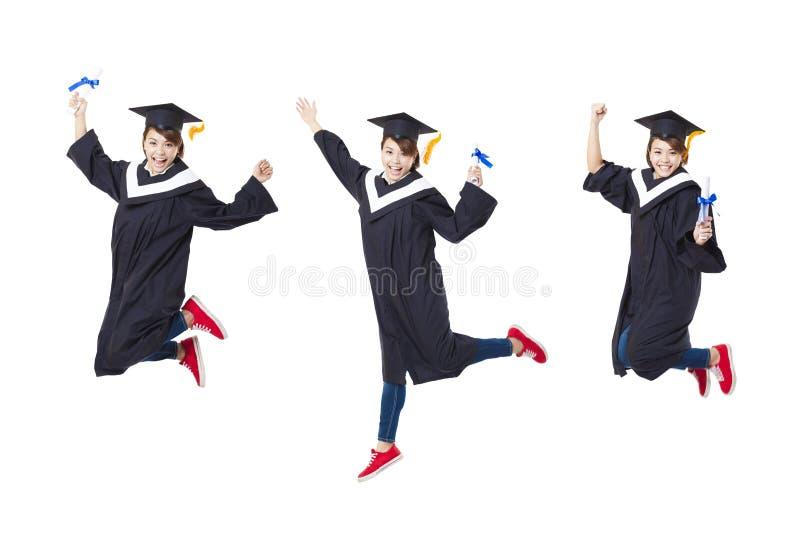 Glücklicher Student in der graduierten Robe, die zurück gegen Weiß springt stockfotos