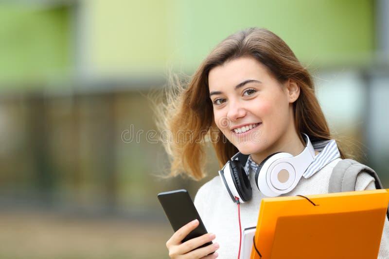 Glücklicher Student, der mit Kopfhörern und Telefon aufwirft stockfoto