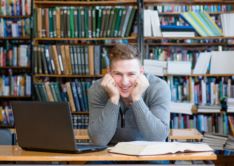Glücklicher Student in der Universitätsbibliothek lizenzfreies stockbild