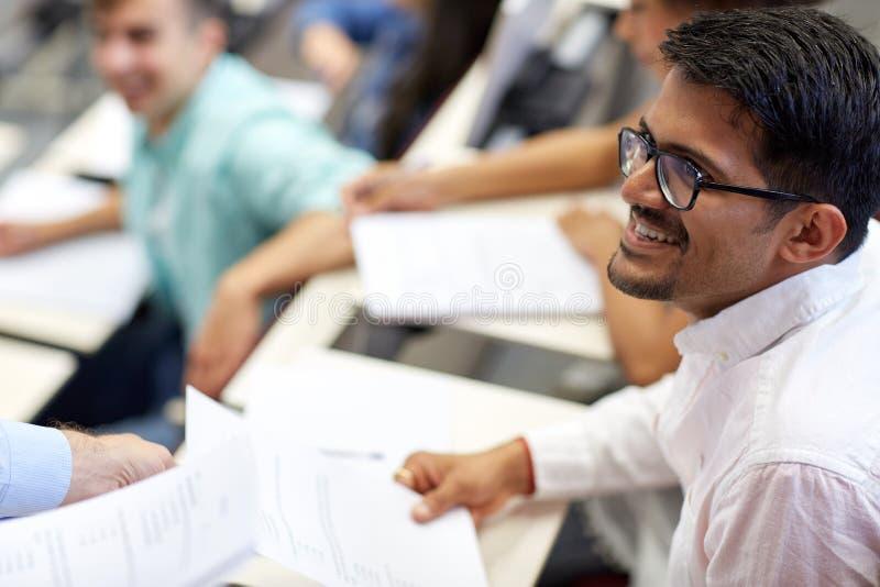 Glücklicher Student mit Prüfungstest oder -mitteilungsblatt am Vortrag lizenzfreie stockfotos