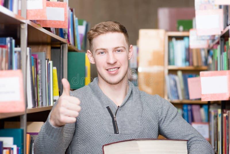 Glücklicher Student mit Stapel bucht das Zeigen von Daumen oben in der Collegebibliothek lizenzfreies stockfoto