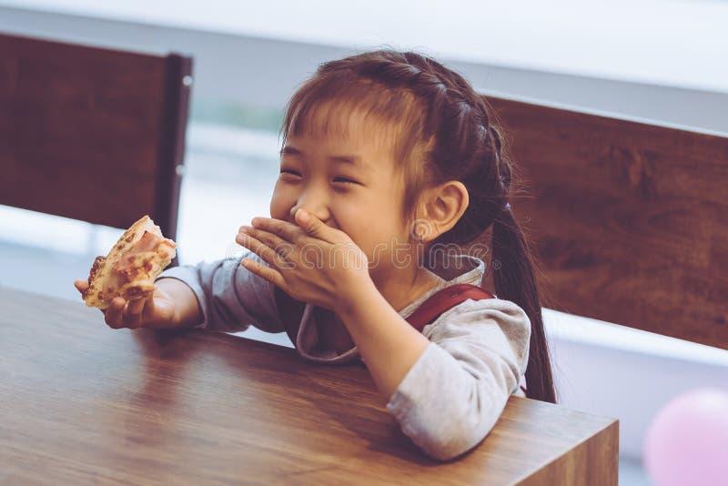 Glücklicher Student scherzt das Essen der Lieferungspizza im Klassenzimmer lizenzfreies stockbild