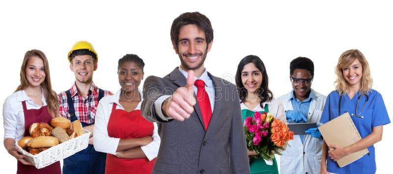 Glücklicher türkischer Geschäftsauszubildender mit Gruppe lateinischen und afrikanischen Lehrlingen stockbilder