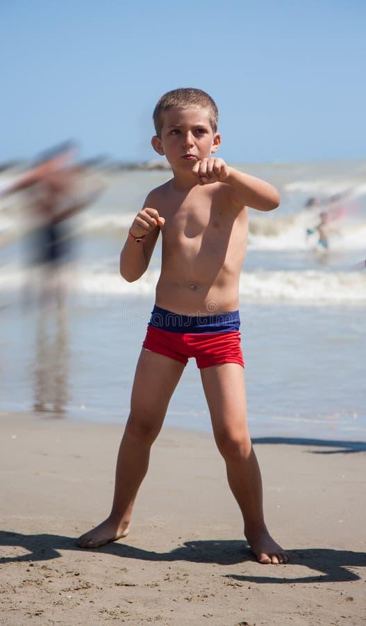Glücklicher Tanz des kleinen Jungen auf Strand zur Tageszeit stockbilder