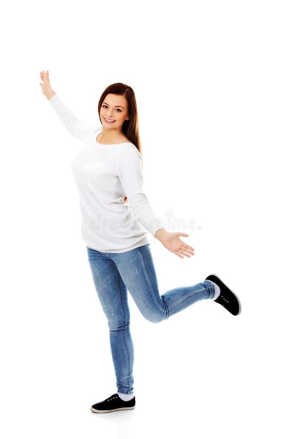 Glücklicher Tanzenjugendlicher mit den Armen oben stockfoto