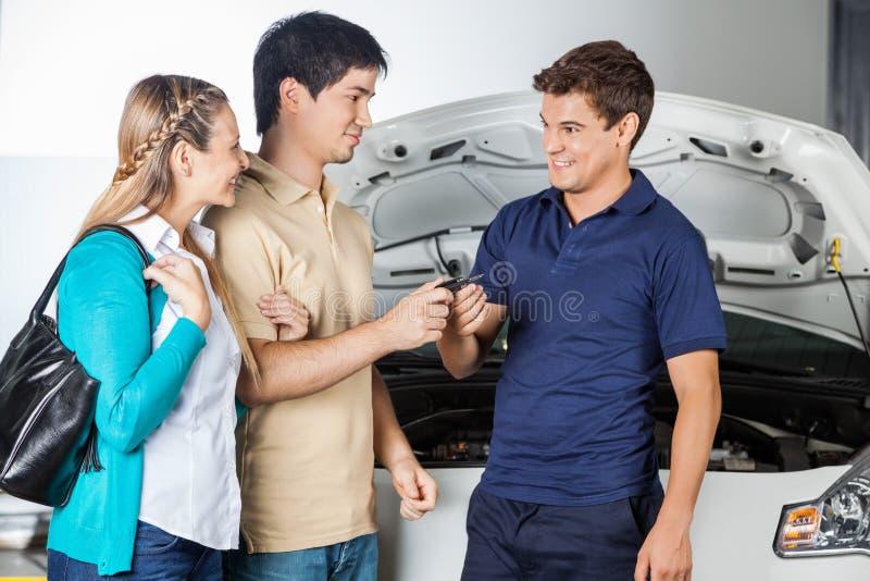 Glücklicher Techniker Taking Car Keys von den Paaren lizenzfreie stockbilder