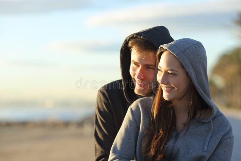 Glücklicher Teenager, der Sonnenuntergang auf dem Strand erwägt lizenzfreie stockbilder
