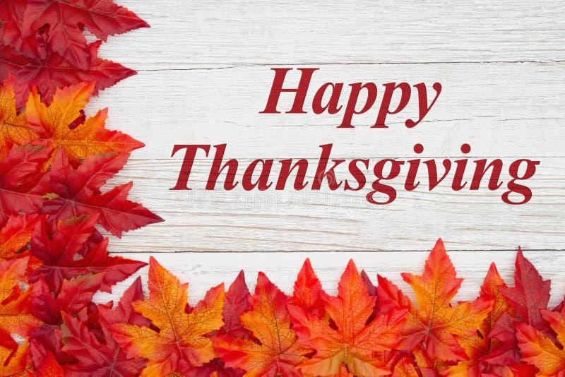 Glücklicher Thanksgiving-Gruß mit roten und orangefarbenen Laub auf verwittertem Holz lizenzfreie stockbilder