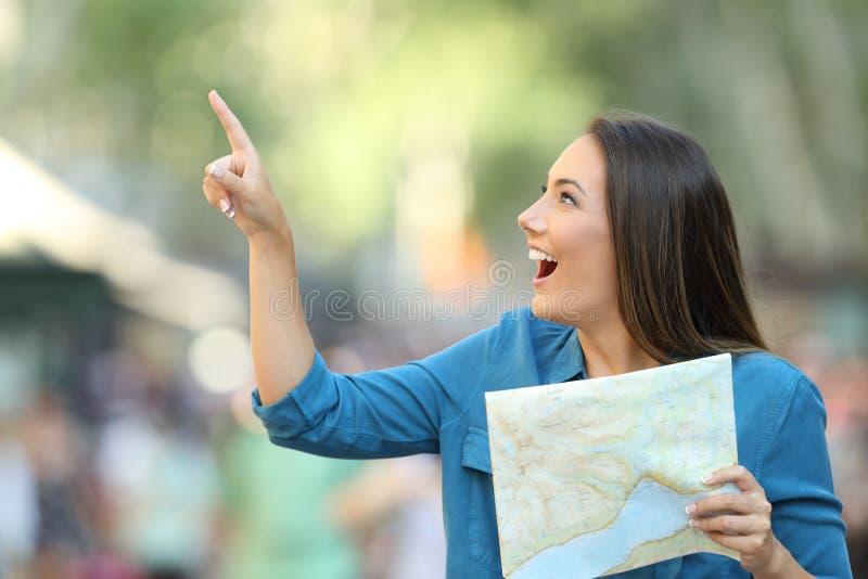 Glücklicher Tourist, der einen Führer zeigt auf Seite hält lizenzfreies stockfoto