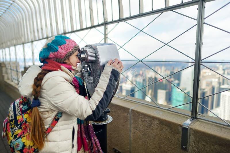 Glücklicher Tourist der jungen Frau an der Aussichtsplattform des Empire State Building in New York City Weiblicher Reisender, de lizenzfreie stockbilder