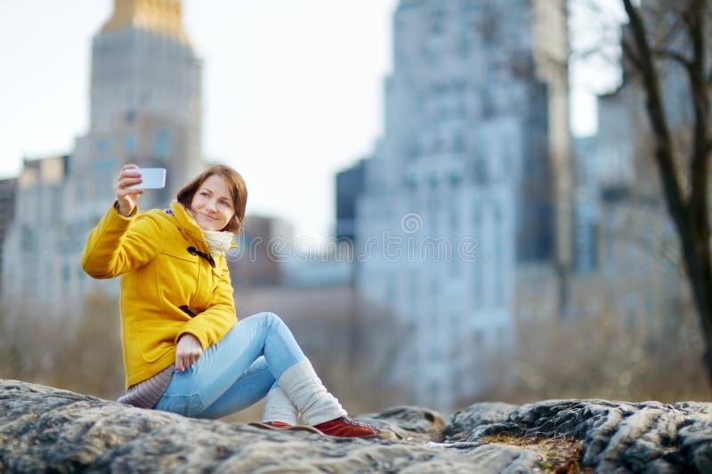 Glücklicher Tourist der jungen Frau, der Fotos am Central Park in New York City macht Weiblicher Reisender, der Ansichten von im  lizenzfreies stockfoto