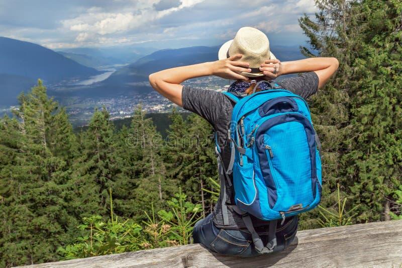 Glücklicher touristischer Mädchenrucksack, der im österreichischen Alpenberg sitzt und Sommer und Natur genießt stockfotos