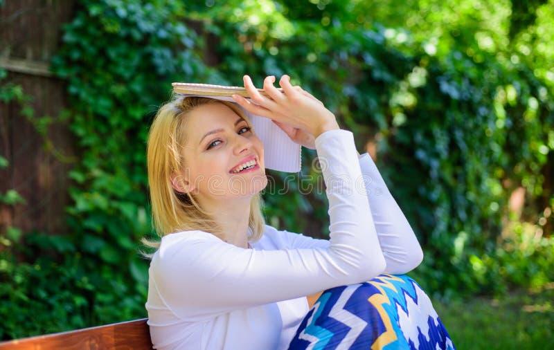 Glücklicher träumerischer gelesener sonniger Tag des Buches hübschen Bücherwurms Dame draußen Mädchen sitzen die Bank, die mit Bu stockbild