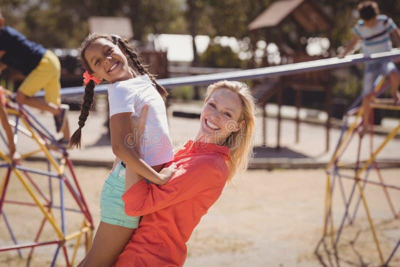 Glücklicher Trainer und Mädchen, die Spielplatz des Spaßes in der Schule hat stockfotografie