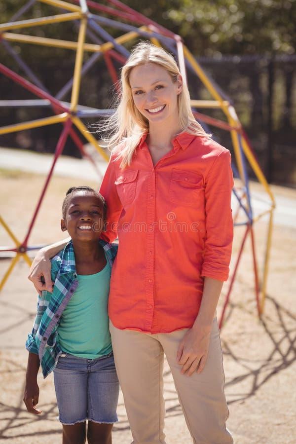 Glücklicher Trainer und Mädchen, die zusammen in der Schule Spielplatz steht stockfoto