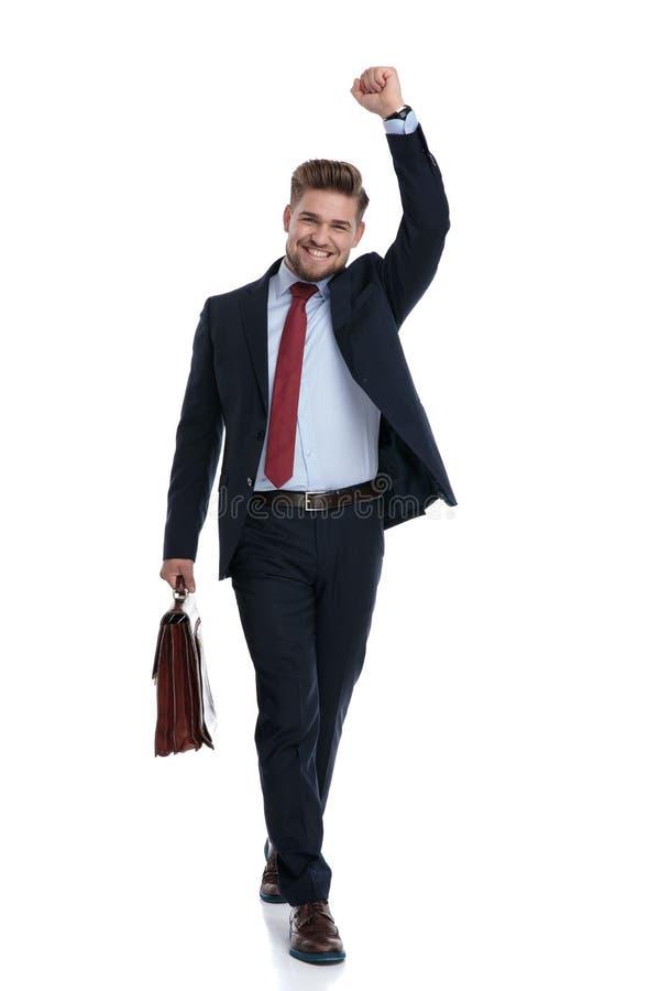 Glücklicher tretender und beim Halten eines Aktenkoffers feiernder Geschäftsmann stockbild