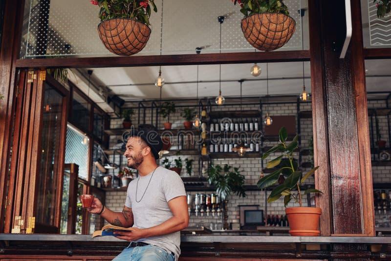 Glücklicher trinkender Kaffee des jungen Mannes und Lesebuch am Café stockfoto