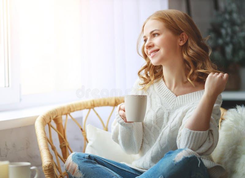 Glücklicher trinkender Morgenkaffee der jungen Frau durch Fenster im Winter lizenzfreie stockfotos
