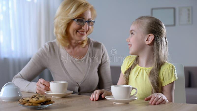 Glücklicher trinkender Tee der Enkelin und der Großmutter und herzlichst lächeln, Familie lizenzfreie stockfotos