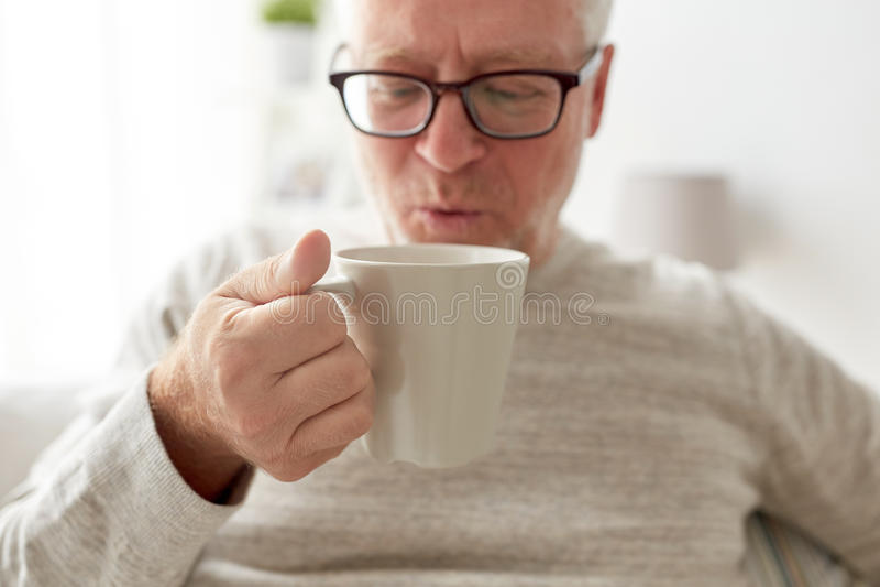 Glücklicher trinkender Tee oder Kaffee des älteren Mannes zu Hause stockbild