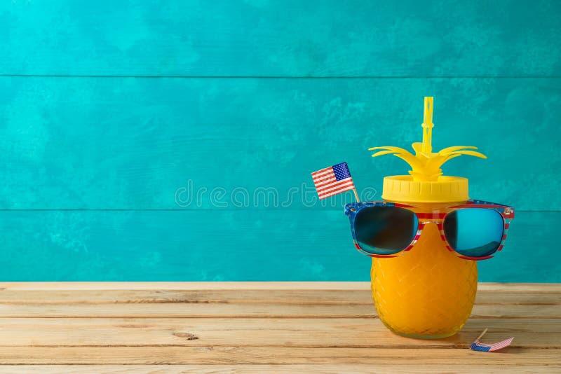 Glücklicher Unabhängigkeitstag, 4. des Juli-Feierkonzeptes mit lustigem Ananasglas und Sonnenbrille auf Holztisch lizenzfreies stockfoto