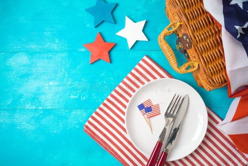 Glücklicher Unabhängigkeitstag, 4. des Juli-Feierkonzeptes mit Picknickkorb, Platte und USA-Flagge auf hölzernem Hintergrund lizenzfreies stockfoto