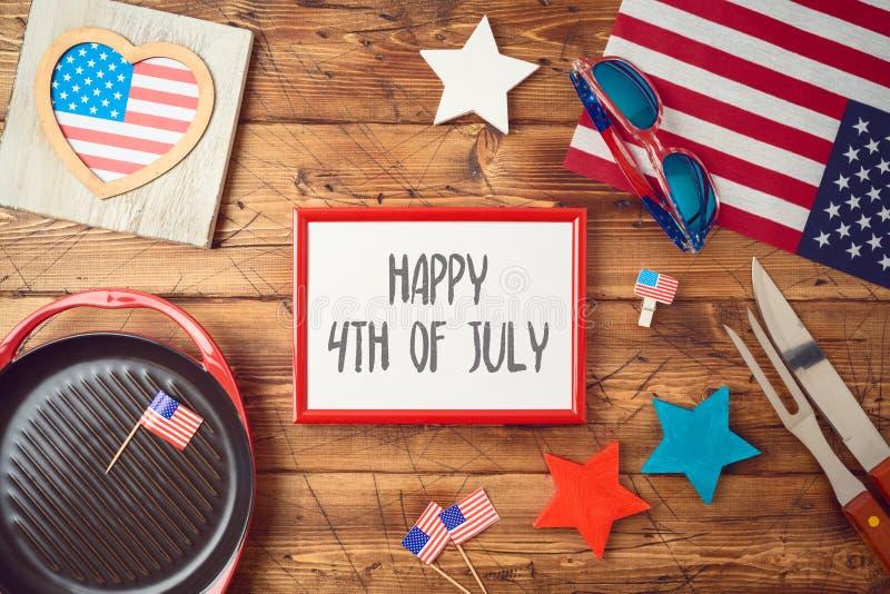 Glücklicher Unabhängigkeitstag, 4. des Juli-Feierkonzeptes mit Rahmen, USA-Flagge und Grillgrill auf hölzernem Hintergrund stockbild