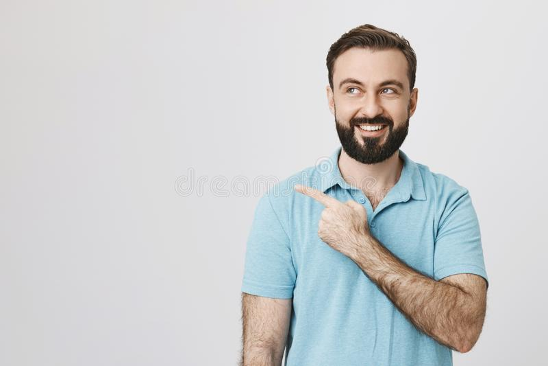 Glücklicher und aufgeregter bärtiger Gatte, der mysteriös lächelt und nach links mit dem Zeigefinger beim, über Grau beiseite sch lizenzfreie stockfotografie