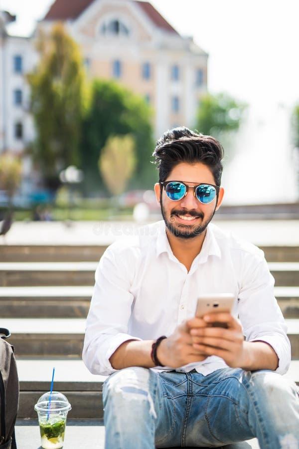Glücklicher und freundlicher junger indischer verwendender oder an intelligentem Telefon und sitzender Treppe arbeitend Mann im F lizenzfreie stockfotografie