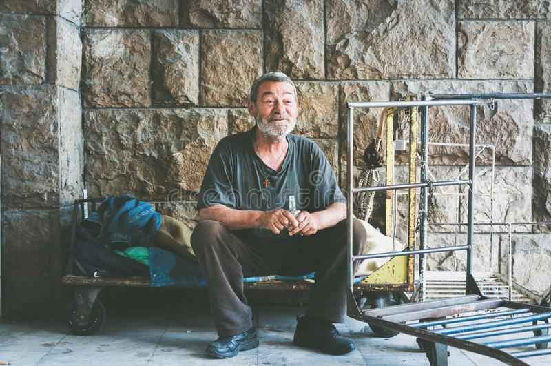 Glücklicher und lächelnder armer obdachloser Mann, der im Schatten des Gebäudes auf der städtischen Straße in der Stadt sitzt stockfoto